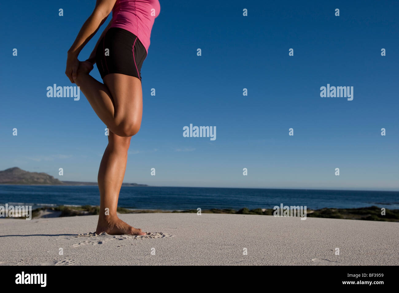 Young Woman barefoot stretches leg - Stock Image