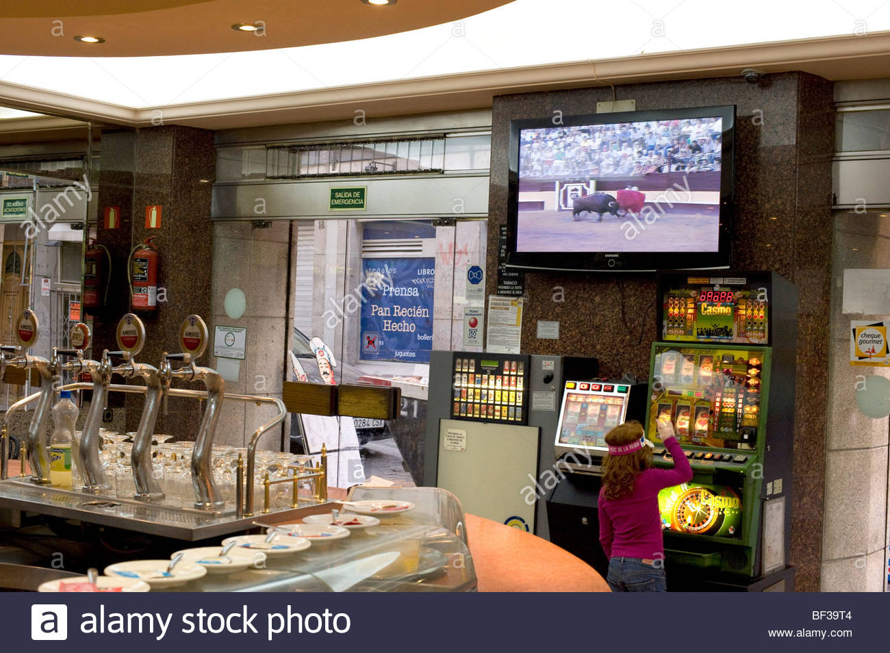 A Bar in Madrid showing bullfighting on a television screen and games machines - Stock Image