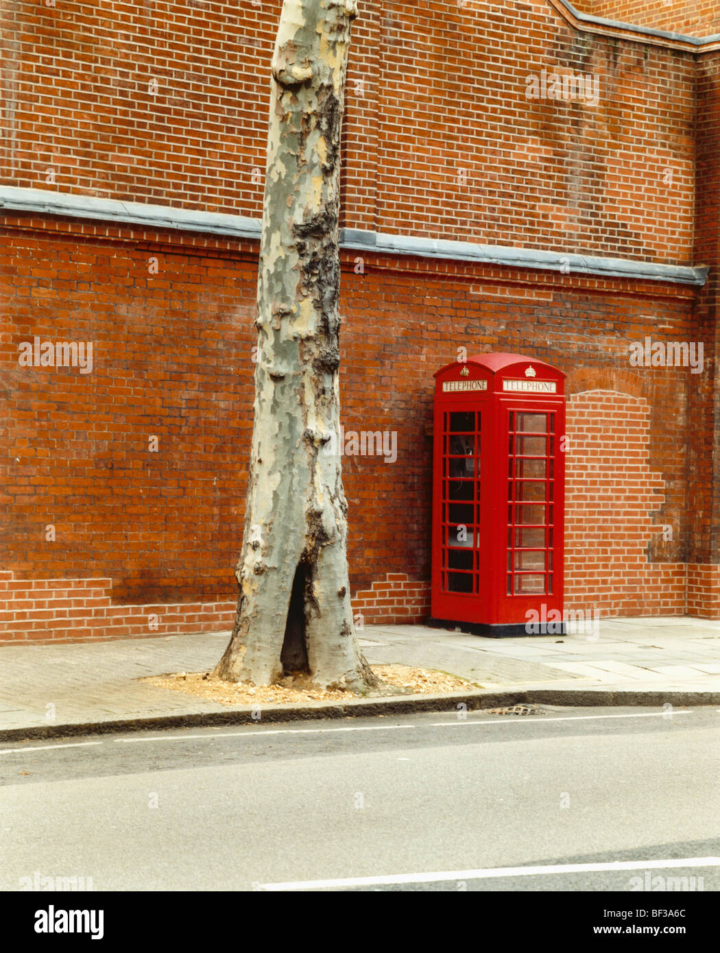 Traditional red phone box in street - Stock Image