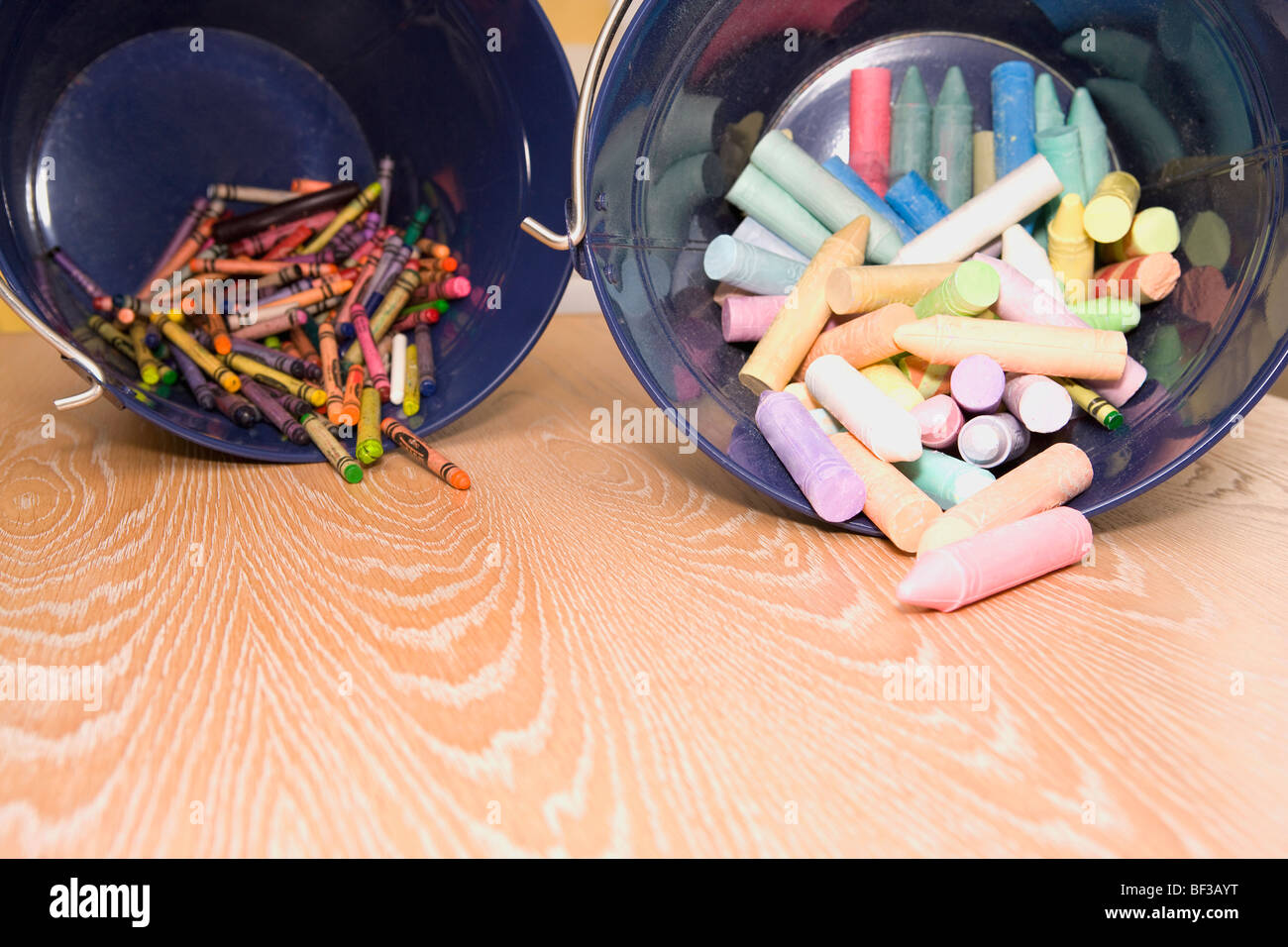 Crayons spilling out from containers - Stock Image