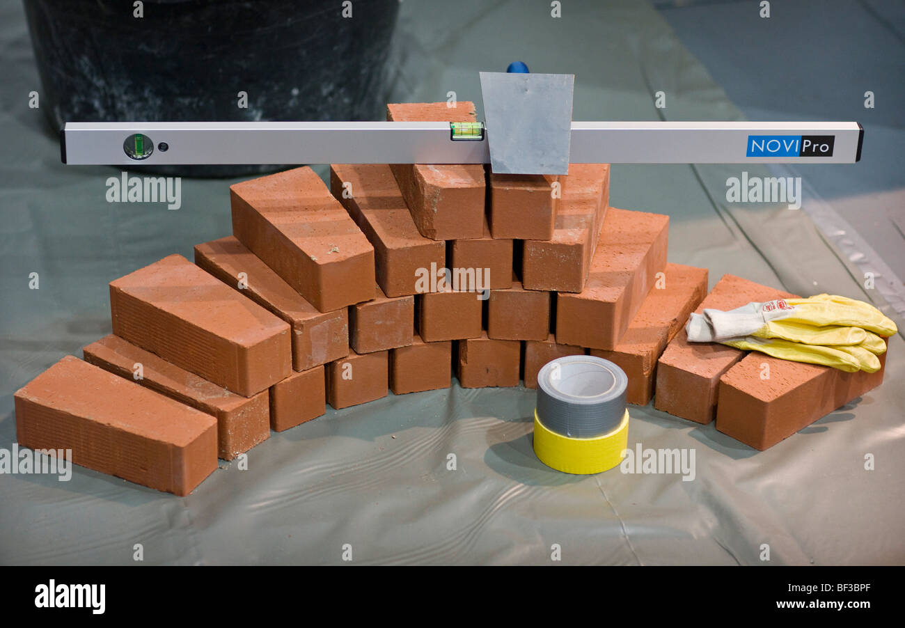 Water level and brick trowel on building bricks - Stock Image