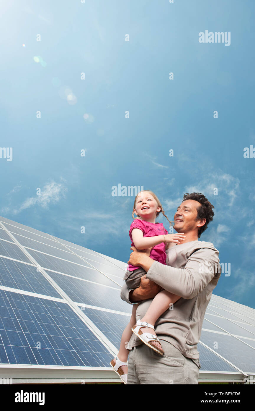 Man and daugther in front of solar panel - Stock Image