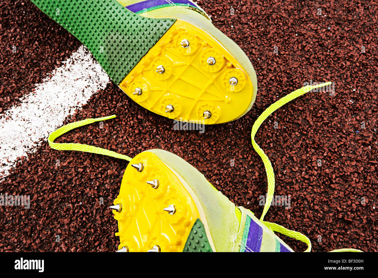 Spiked running shoes on track - Stock Image