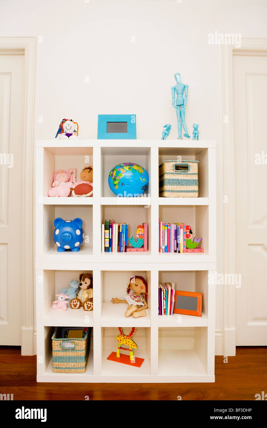 Toys and books in a shelf - Stock Image