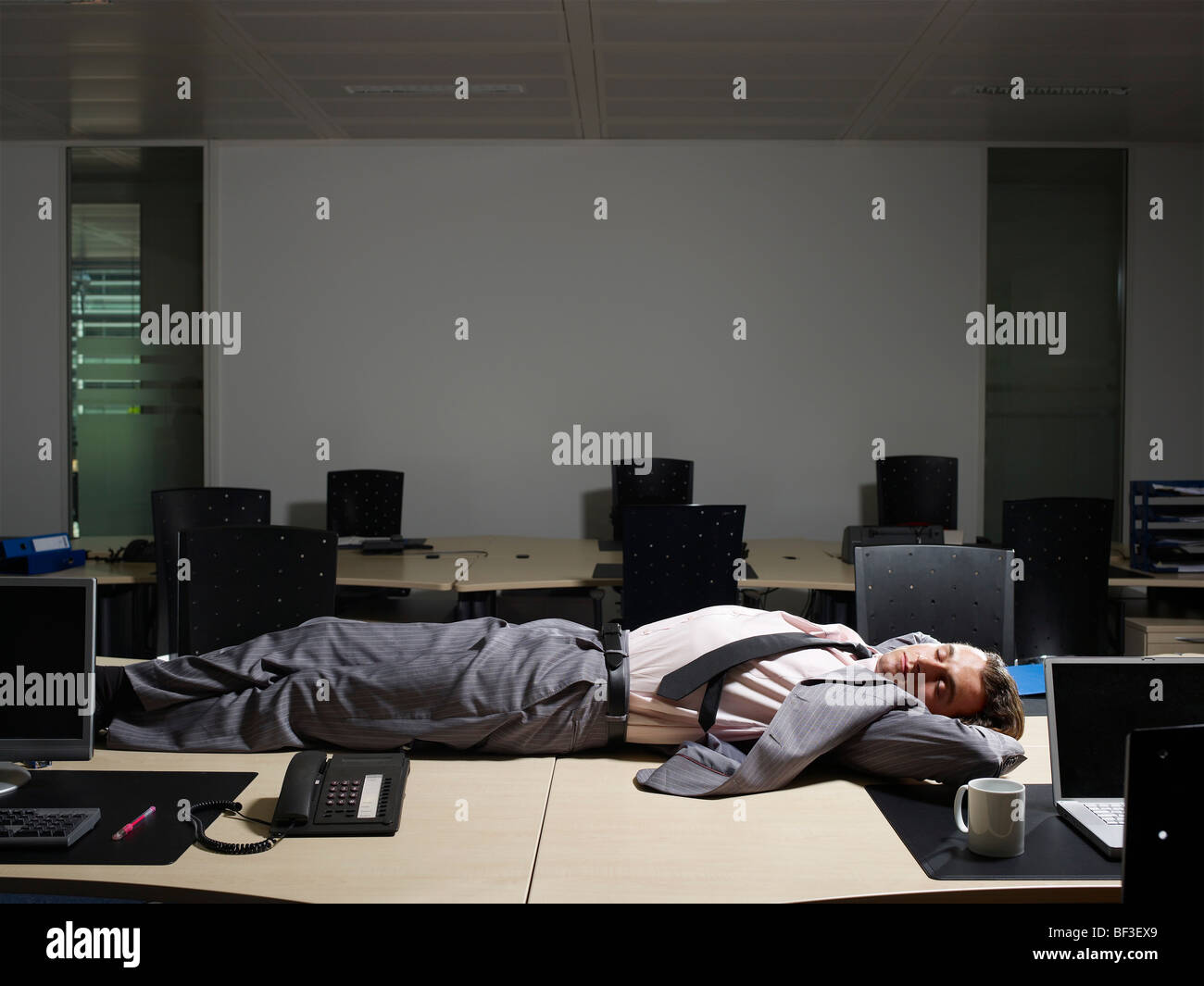 A man sleeps at his desk - Stock Image