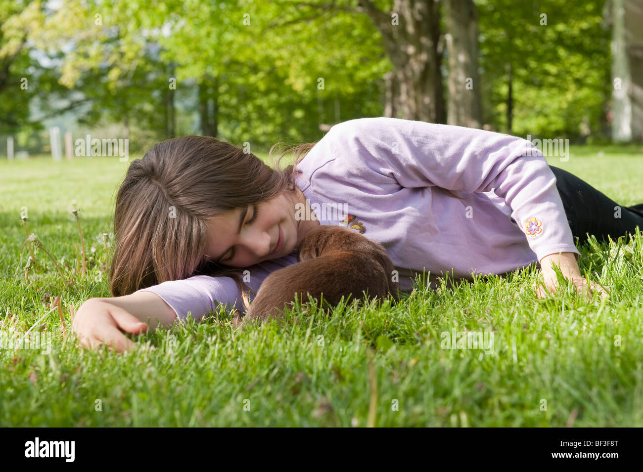 Adolescent cuddling puppy - Stock Image