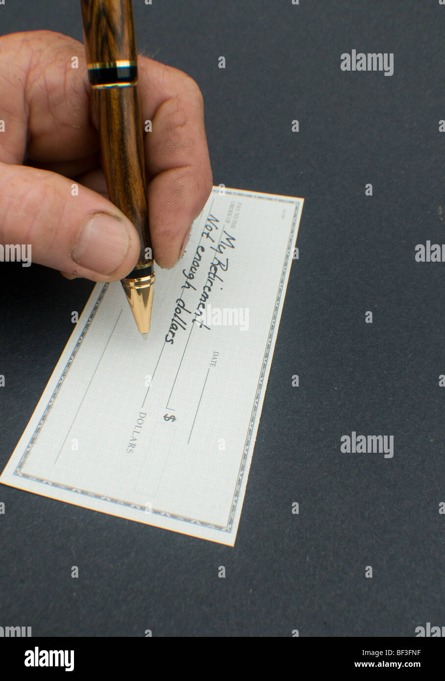 male hand writing check to my retirement for not enough dollars - Stock Image