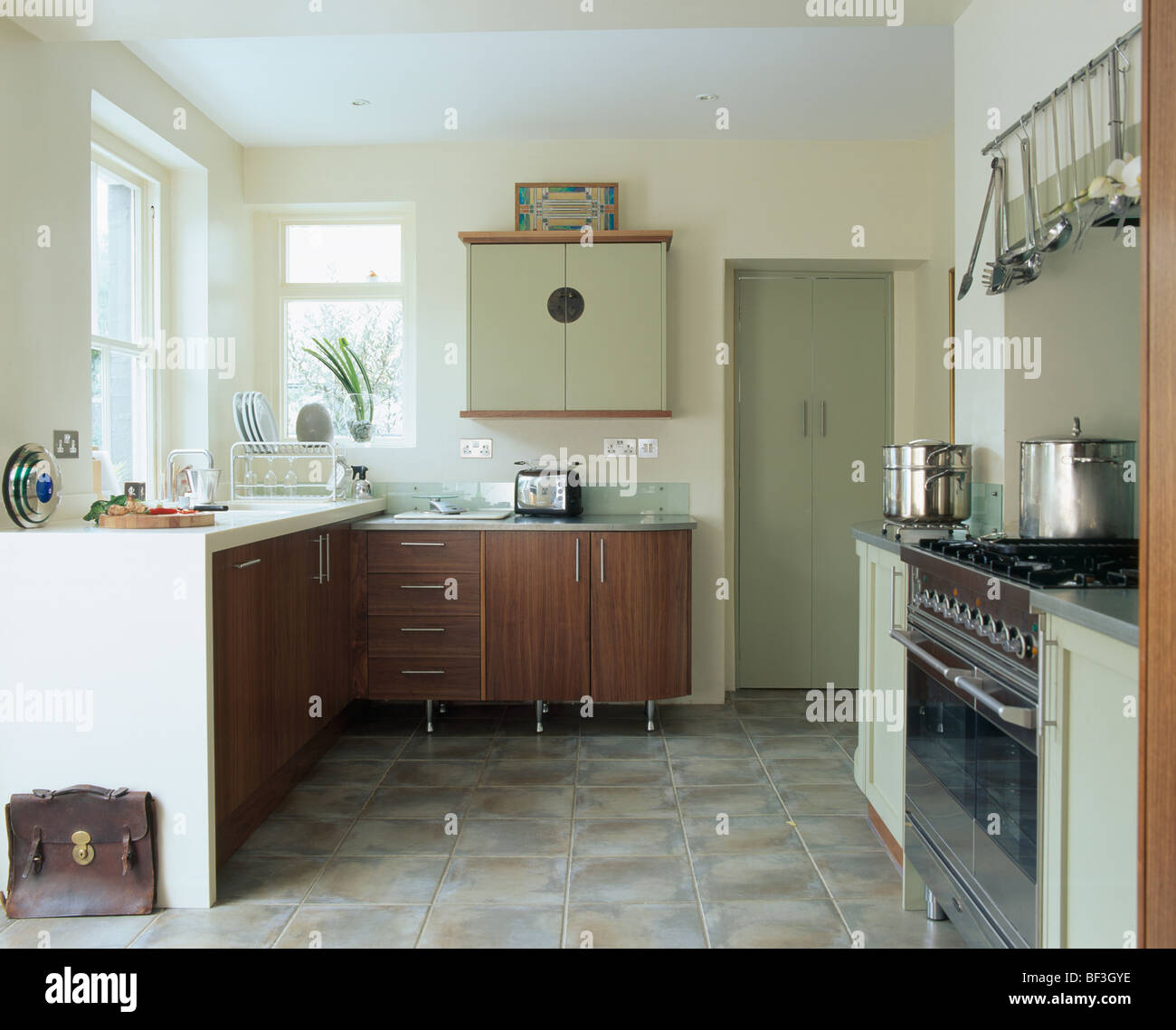 Modern kitchen with dark wood units and pale green wall cupboard and slate flooring