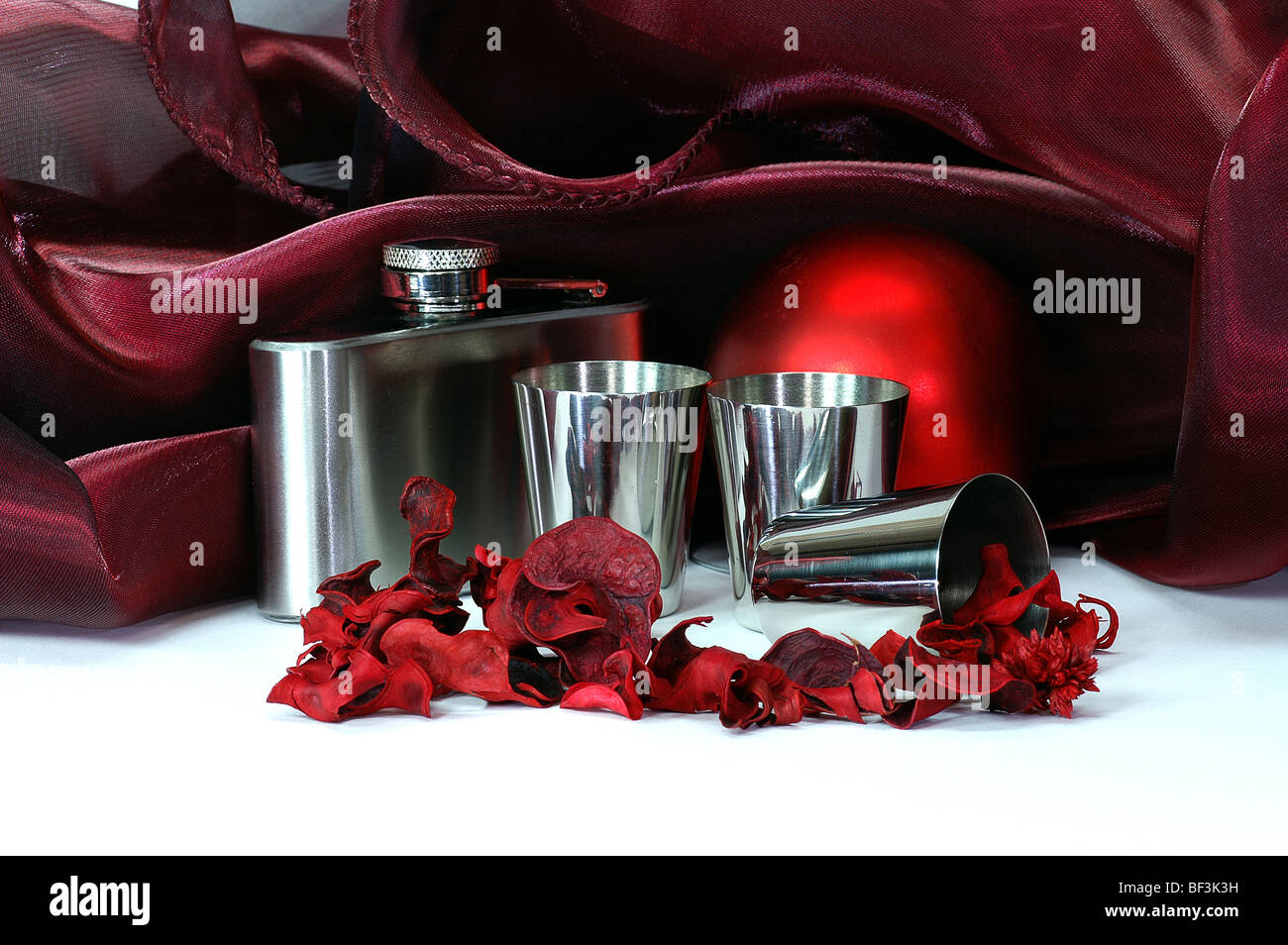still life in crimson tints with shpere, flask, steell cups, colored dried plants, drapery and other objects - Stock Image