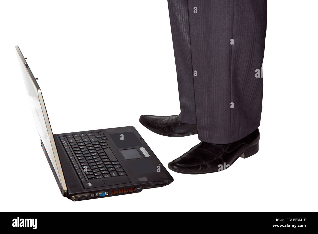The opened laptop lies on a floor and nearby there is a man Stock Photo
