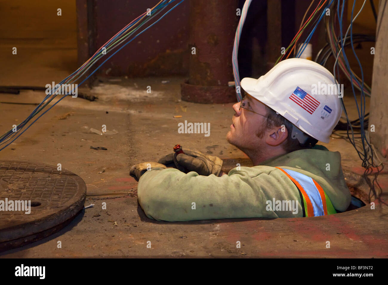 Chicago, Illinois - A public employee works on electrical wiring in a manhole. - Stock Image