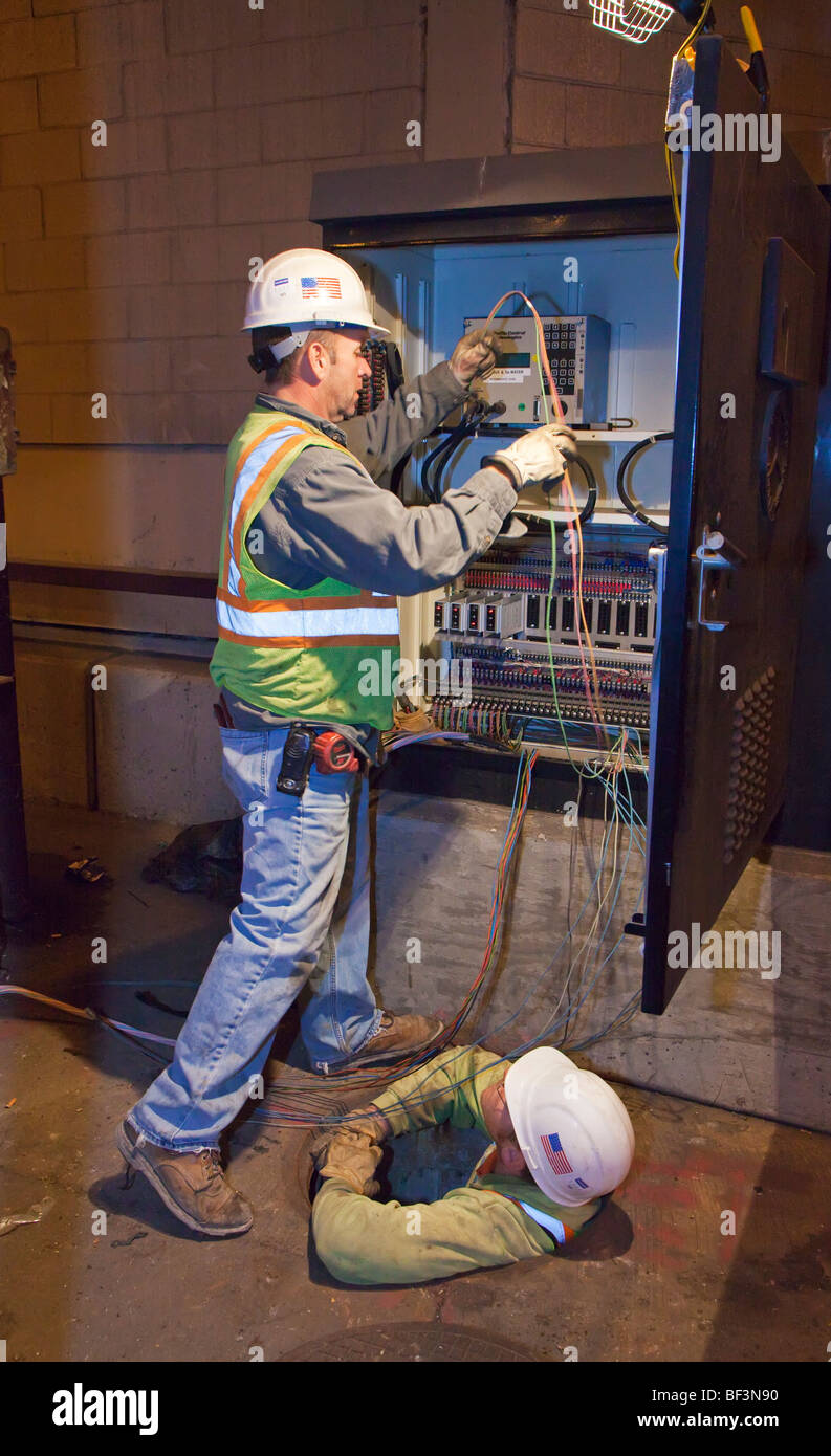 Chicago, Illinois - Public employees working on electrical wiring. - Stock Image