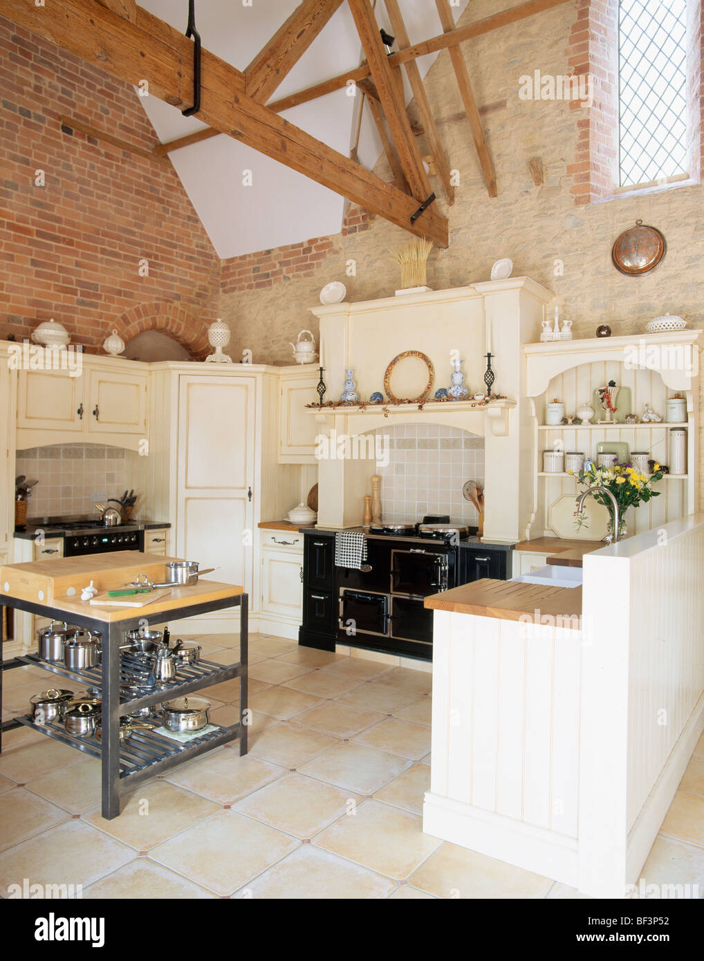 Black Aga Oven And Limestone Flooring In Barn Conversion Kitchen With  Saucepanu0027s On Shelves On Modern Butcheru0027s Block