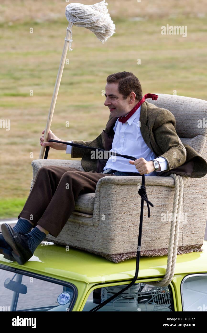 Mr Bean Frohe Weihnachten.Rowan Atkinson Aka Mr Bean Rides An Armchair On The Roof Of A Mini