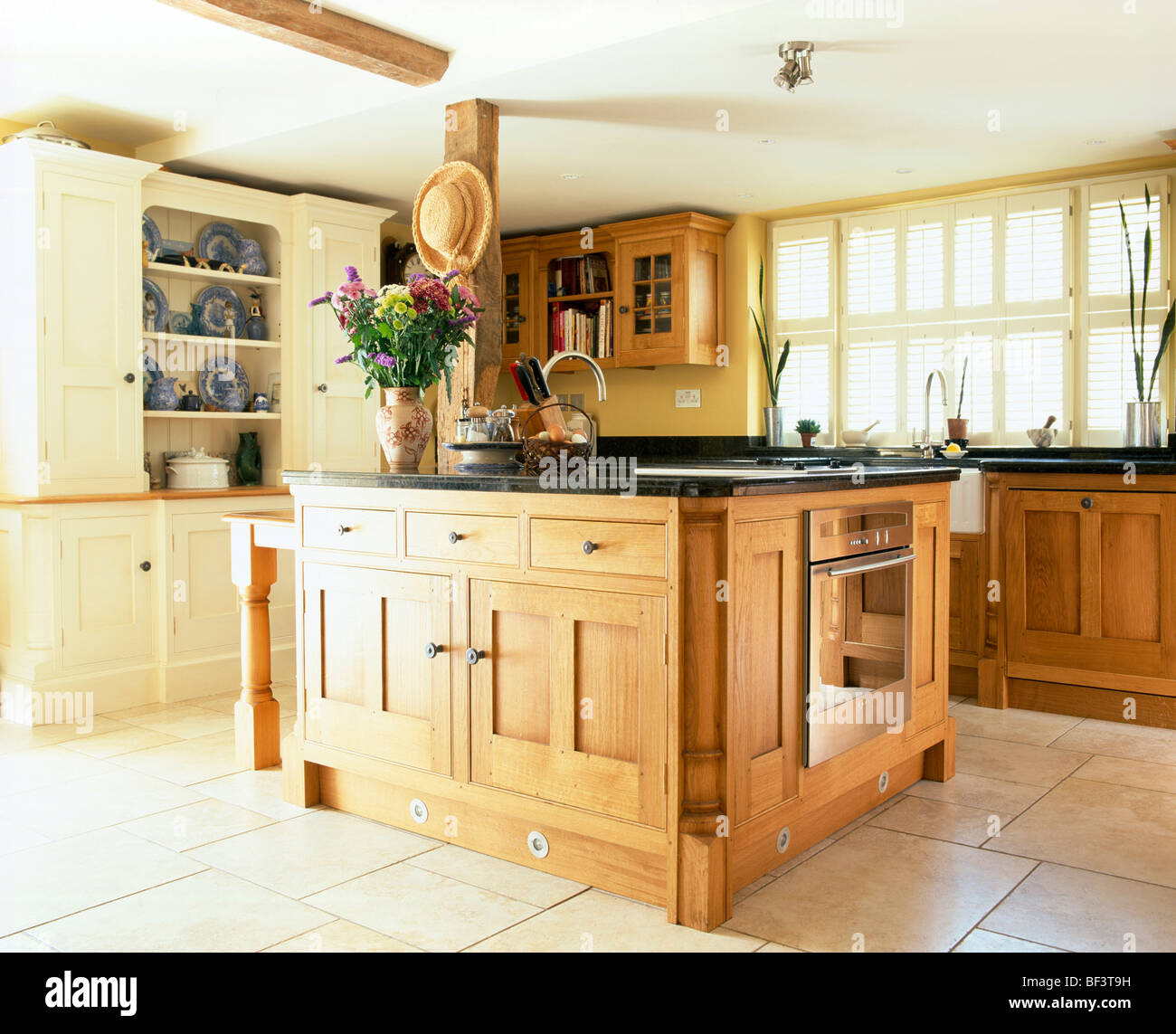 Pale wood island unit with sink and oven in traditional country ...