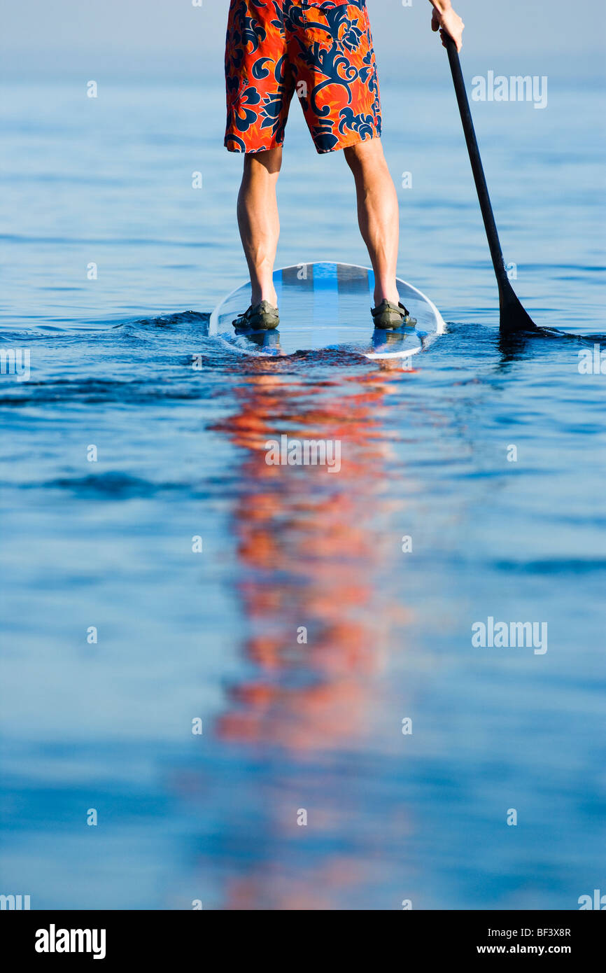 Close up of a man from waist down on a standup paddle board. - Stock Image
