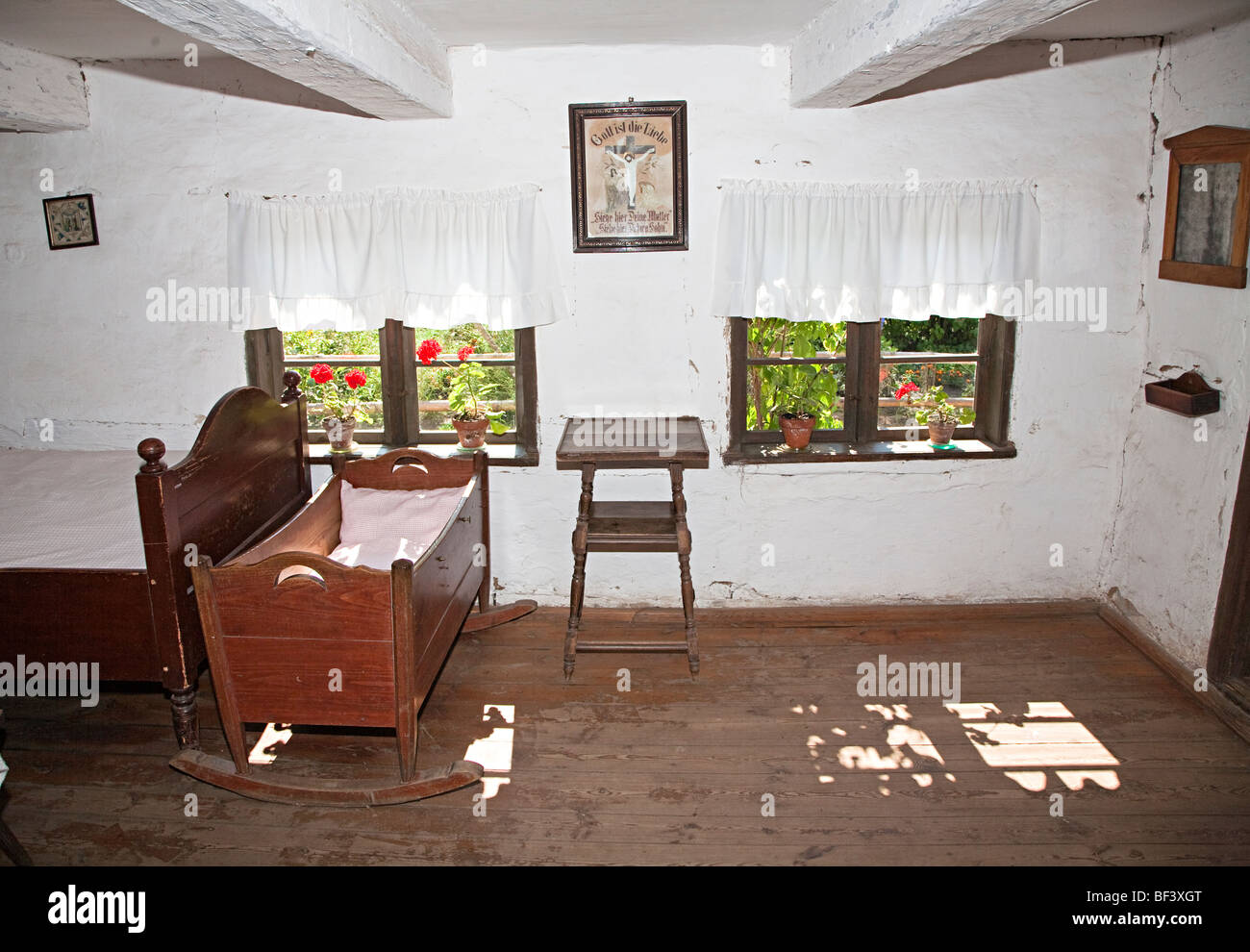 Bedroom in the Reimann family farmhouse with religious poster on wall Kluki open air folk museum Poland - Stock Image