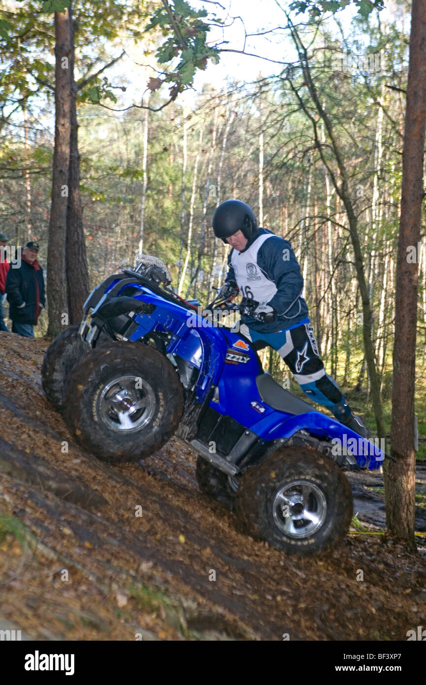 Man rides all-terrain vehicle (ATV) on steep terrain in woods. Trial off-road biking - Stock Image