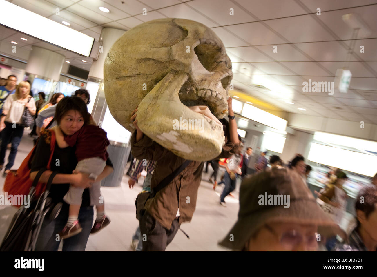 A man exits a train line carrying a huge fibre glass skull, in Shibuya, in Tokyo, Japan, on Saturday 26th September - Stock Image