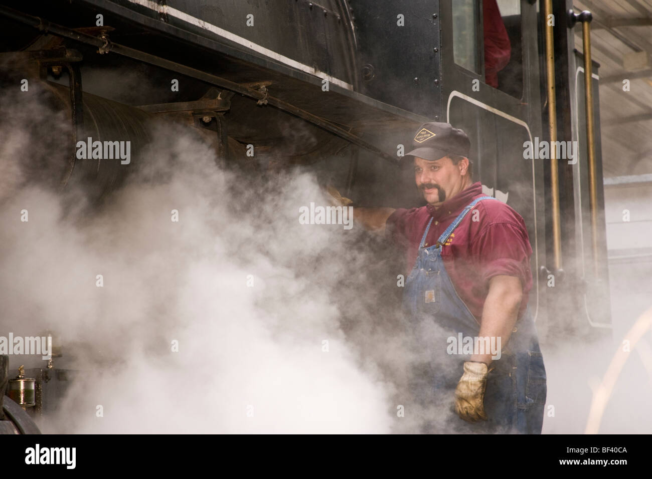 Engineer bleeding steam from the number 75 Flagg Coal locomotive, a 1930 steam engine - Stock Image