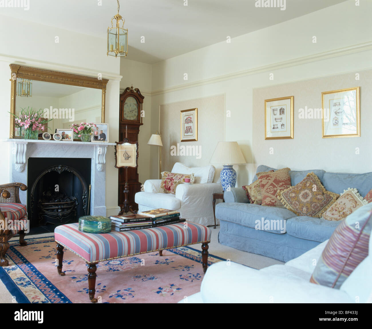 Striped upholstered stool on pink Chinese rug in front of fireplace ...