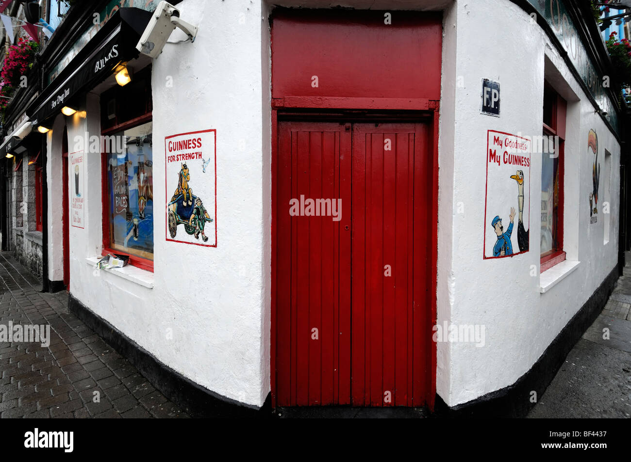 frontal front street frontage view the dewdrop inn bar pub licensed premises galway ireland red door closed shut - Stock Image