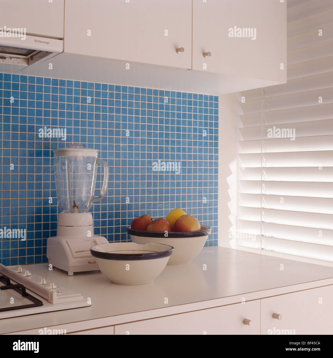 Electric blender and blue+white bowls on white worktop below blue ...