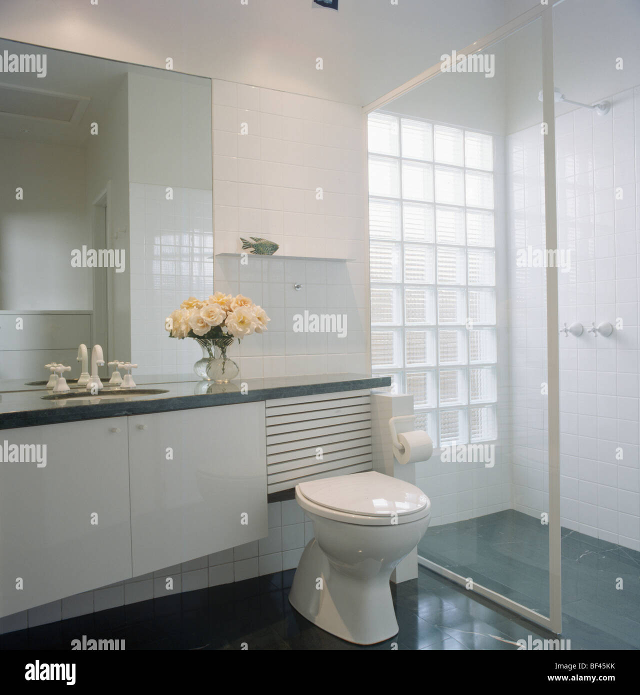 Glass door on walk-in shower in modern white bathroom with glass ...