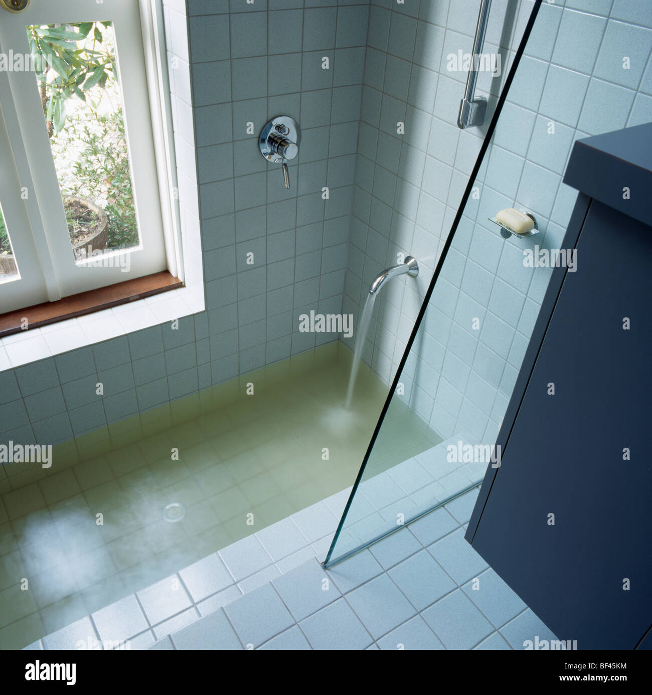 Water pouring from chrome tap into sunken bath with glass shower ...