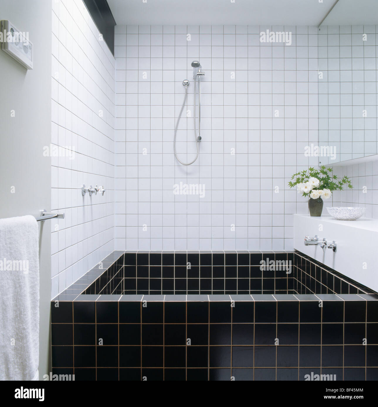 Shower above square black tiled bath in modern white tiled bathroom ...