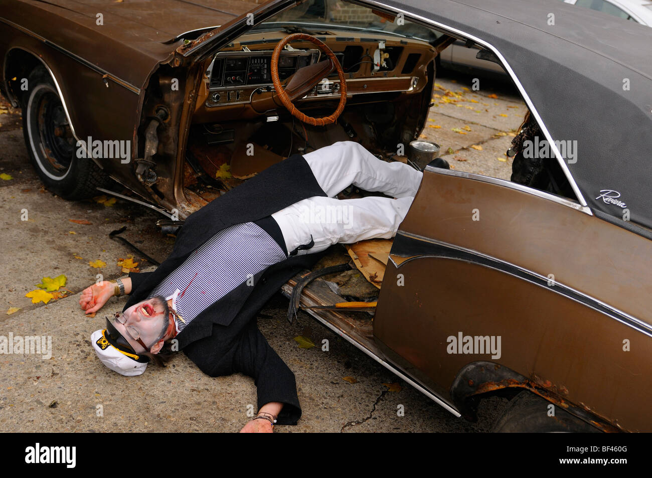 Undead sailor splayed out on a junked Buick Riviera car play acting at the Toronto Zombie Walk - Stock Image