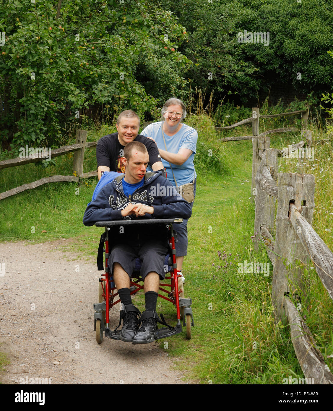 Disabled boy being pushed along by loving parents. - Stock Image