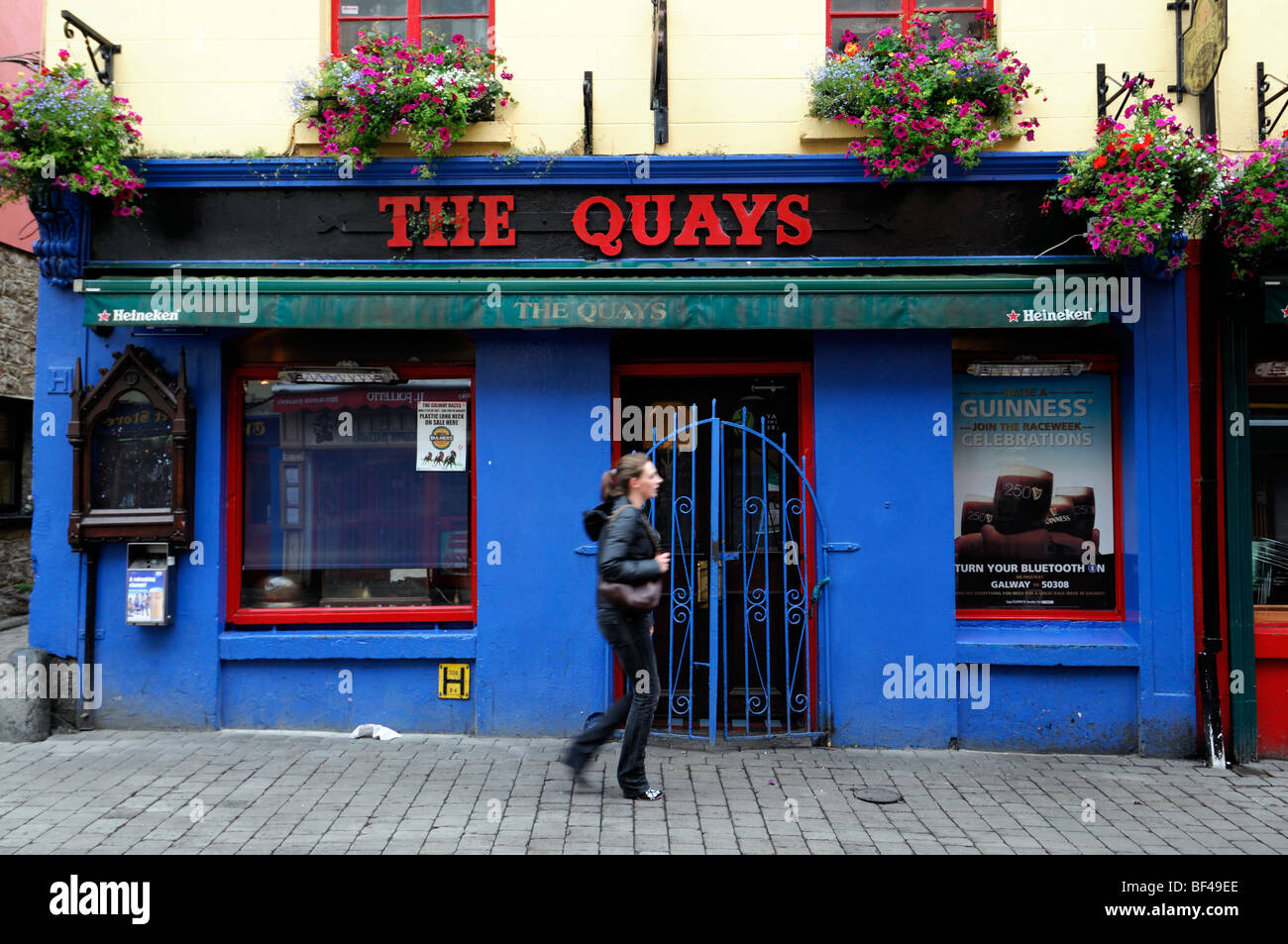 frontal front street frontage view the quays bar pub licensed premises galway ireland blue closed shut not open - Stock Image