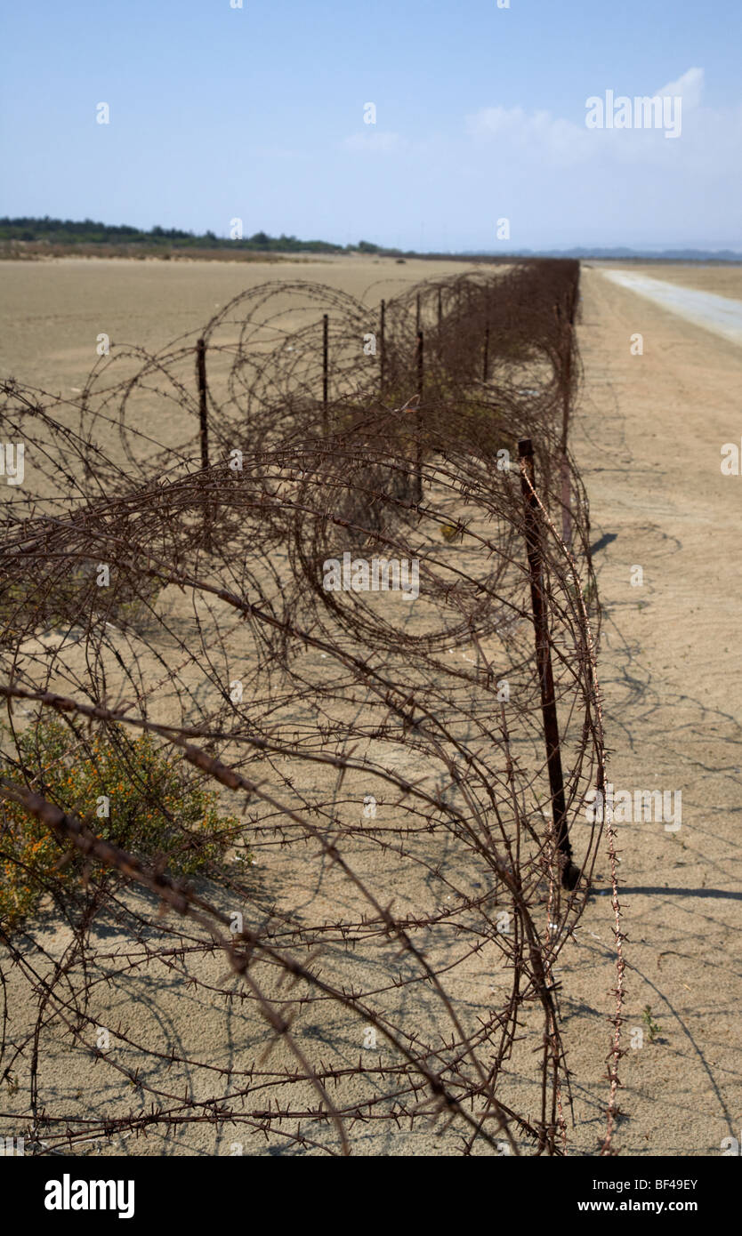 rusty barbed wire fence on the akrotiri salt flats the limit of the western Sovereign Base Area SBA in the republic Stock Photo