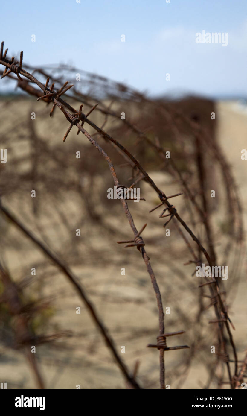 rusty barbed wire fence on the akrotiri salt flats the limit of the western Sovereign Base Area SBA in the republic - Stock Image