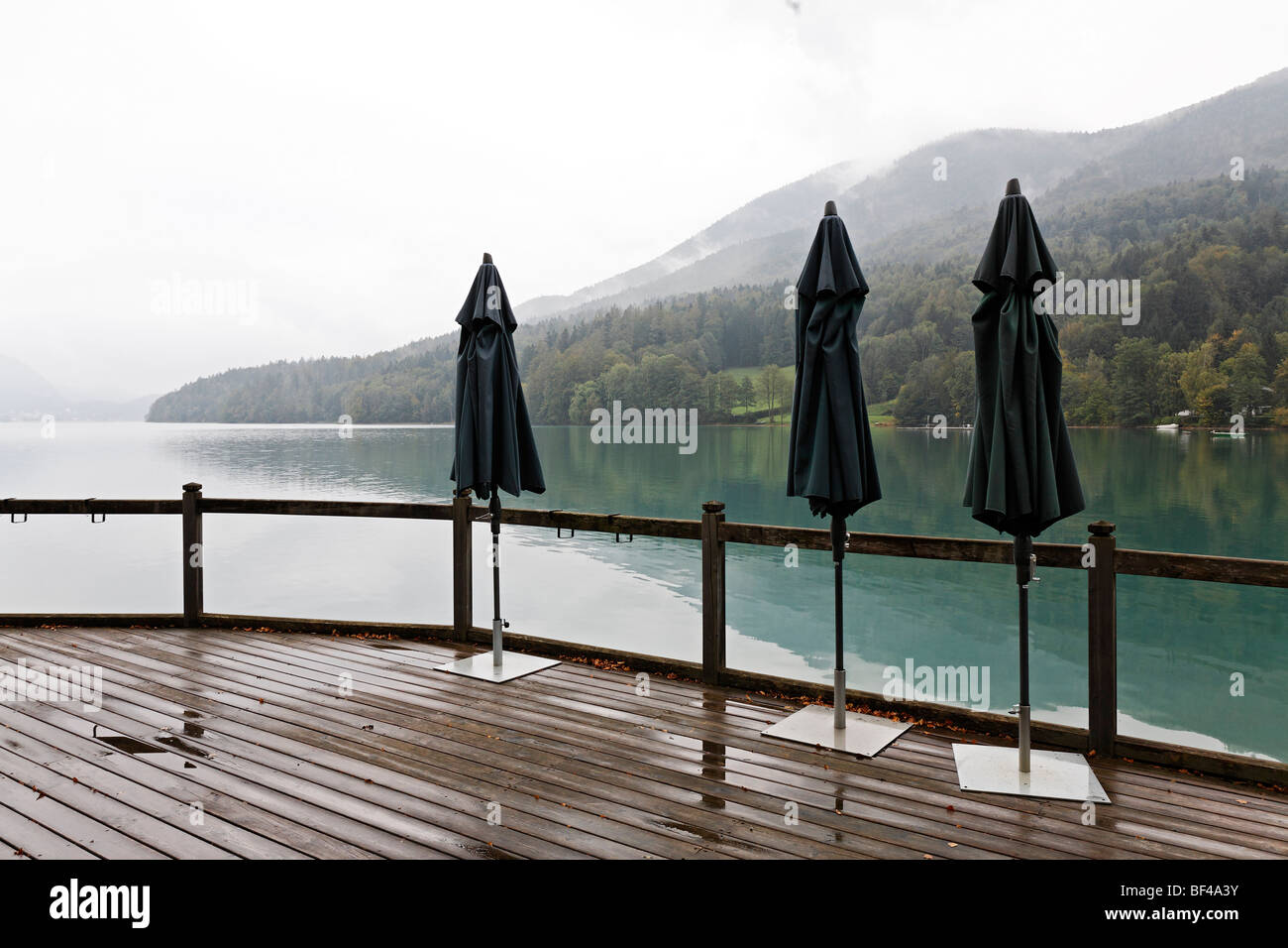 Three closed parasols, terrace on the lake, overcast sky, rainy, dreary atmosphere, Fuschlsee lake, Salzkammergut - Stock Image