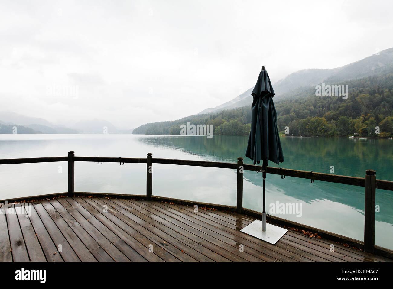 Single closed parasol, terrace on the lake, overcast sky, rainy, dreary atmosphere, Fuschlsee lake, Salzkammergut - Stock Image