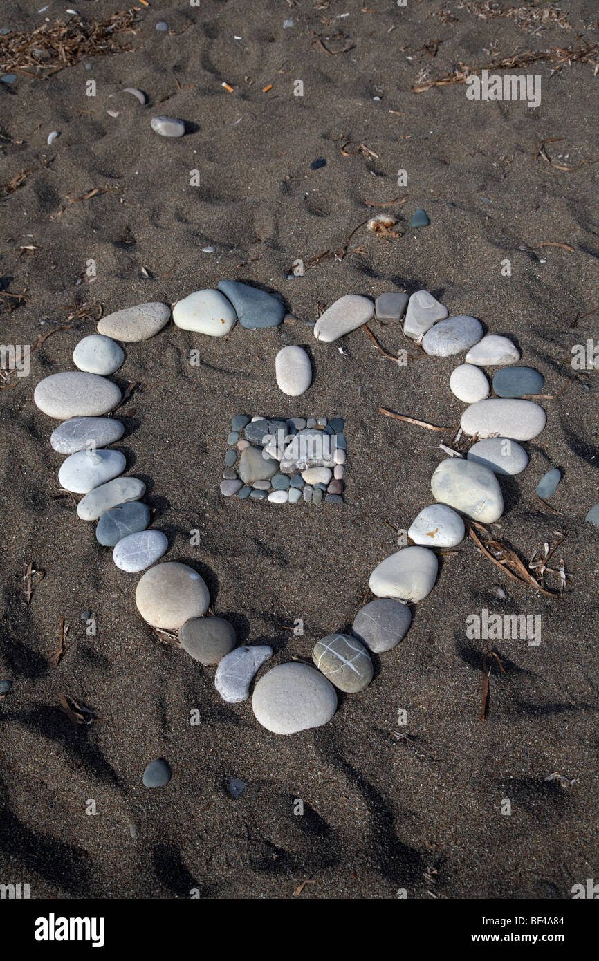 heart symbol made out of pebbles on the beach at aphrodites rock petra tou romiou republic of cyprus europe - Stock Image