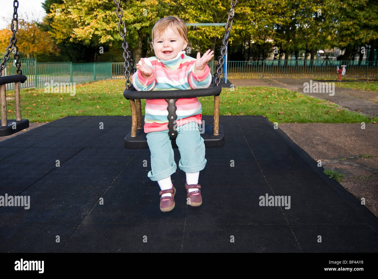 Horizontal close up portrait of a little girl smiling and clapping whilst sitting on a swing at the park in the Stock Photo