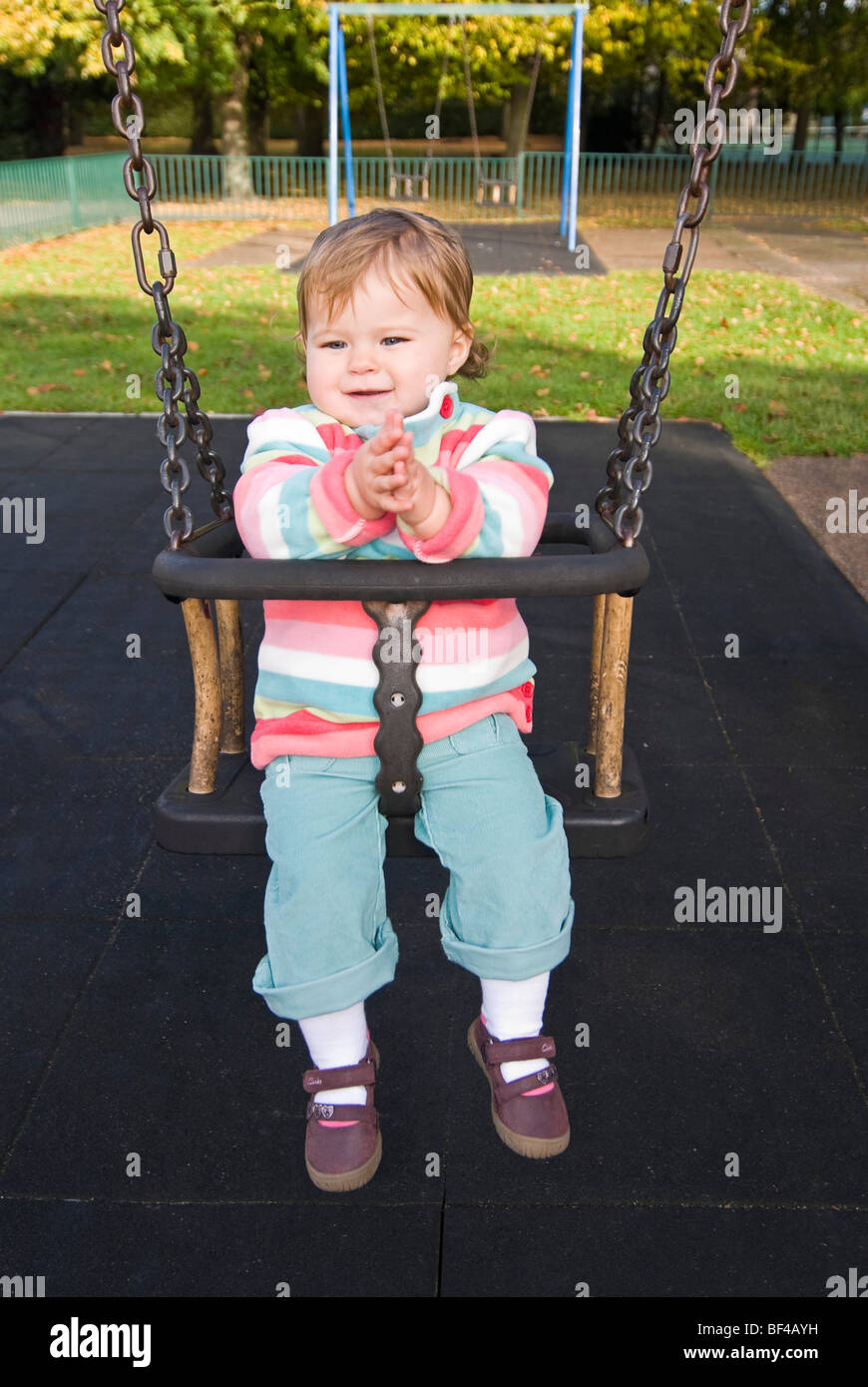 Vertical close up portrait of a little girl smiling and clapping whilst sitting on a swing at the park in the sunshine. Stock Photo