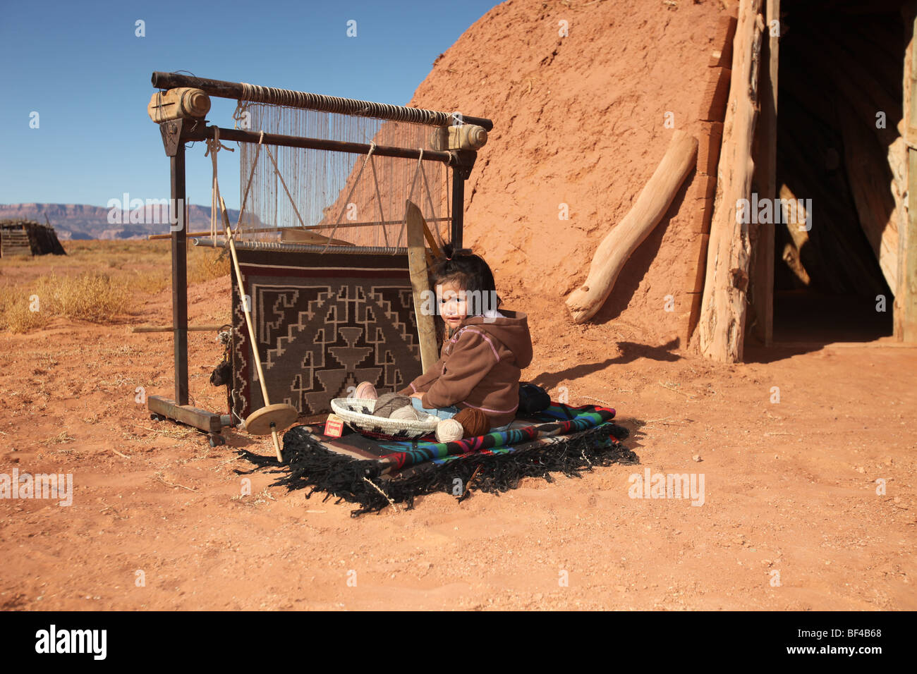Native Navajo Child Sitting Next to Traditional Rug Making Tools - Stock Image
