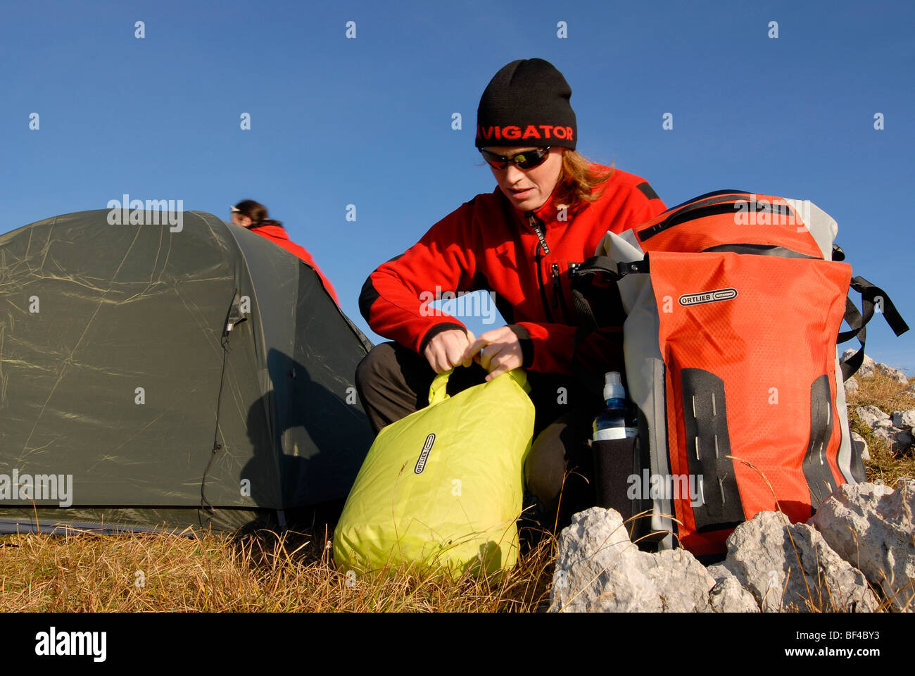 Hikers, young man and woman buildig a bivouac with tent, sleeping bag, backpack and sleeping pad, Mt. Heidachstellwand, - Stock Image