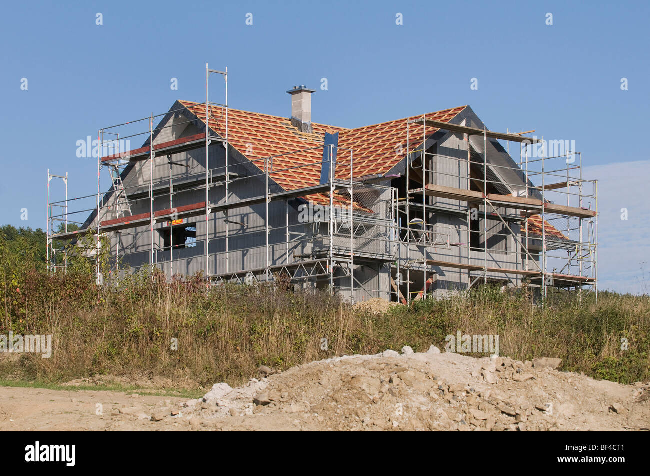 Housing construction, scaffolded new apartment house, in front, a dirt mound - Stock Image