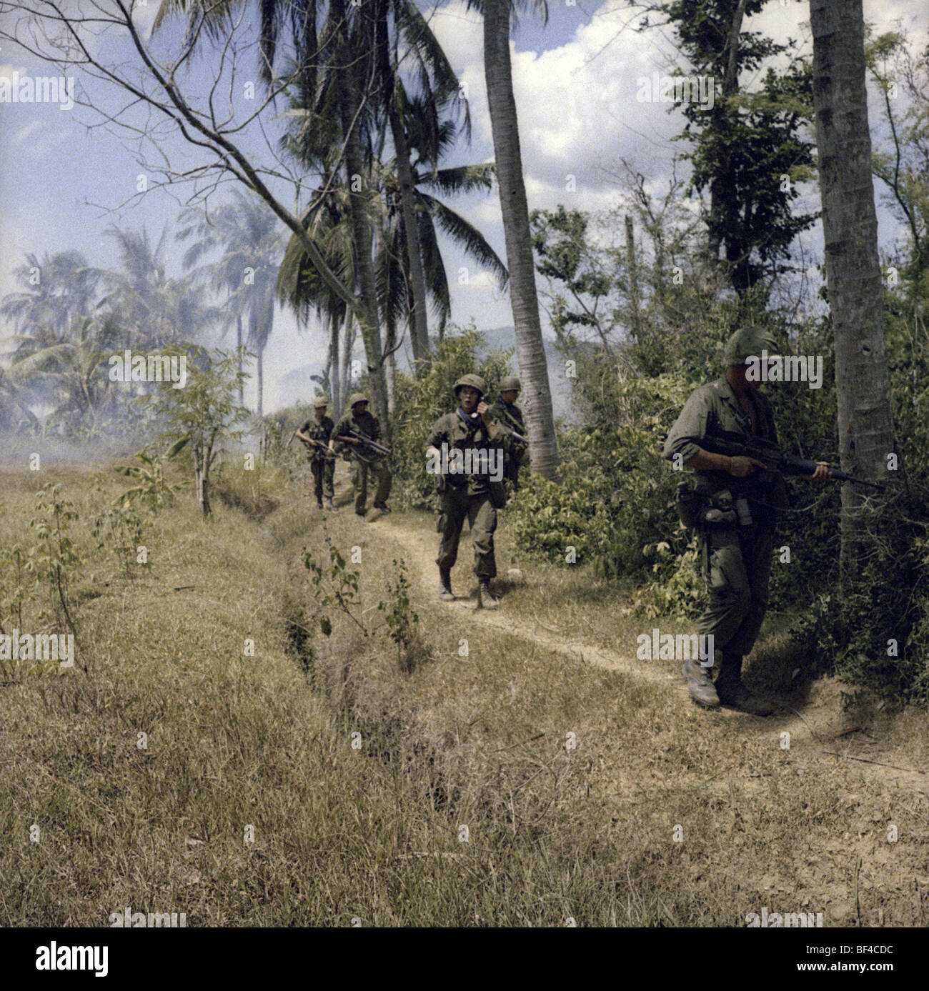 Infantrymen of B Troop, 1st Squadron, 9th Cavalry walk on patrol during the Vietnam War in 1967. - Stock Image