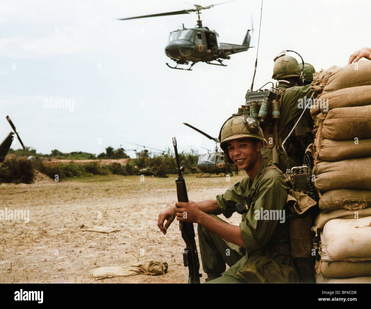 A Huey gunship helicopter of B Troop, 1st Squadron, 9th Cavalry prepares to land while soldiers wait at an LZ. - Stock Image