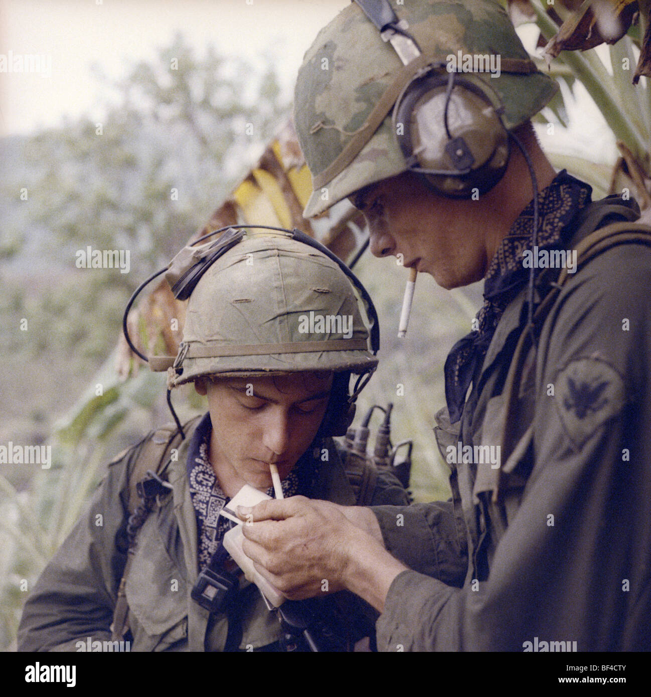 Members of B Troop, 1st Squadron, 9th Cavalry light a cigarette during the Vietnam War in 1967. - Stock Image