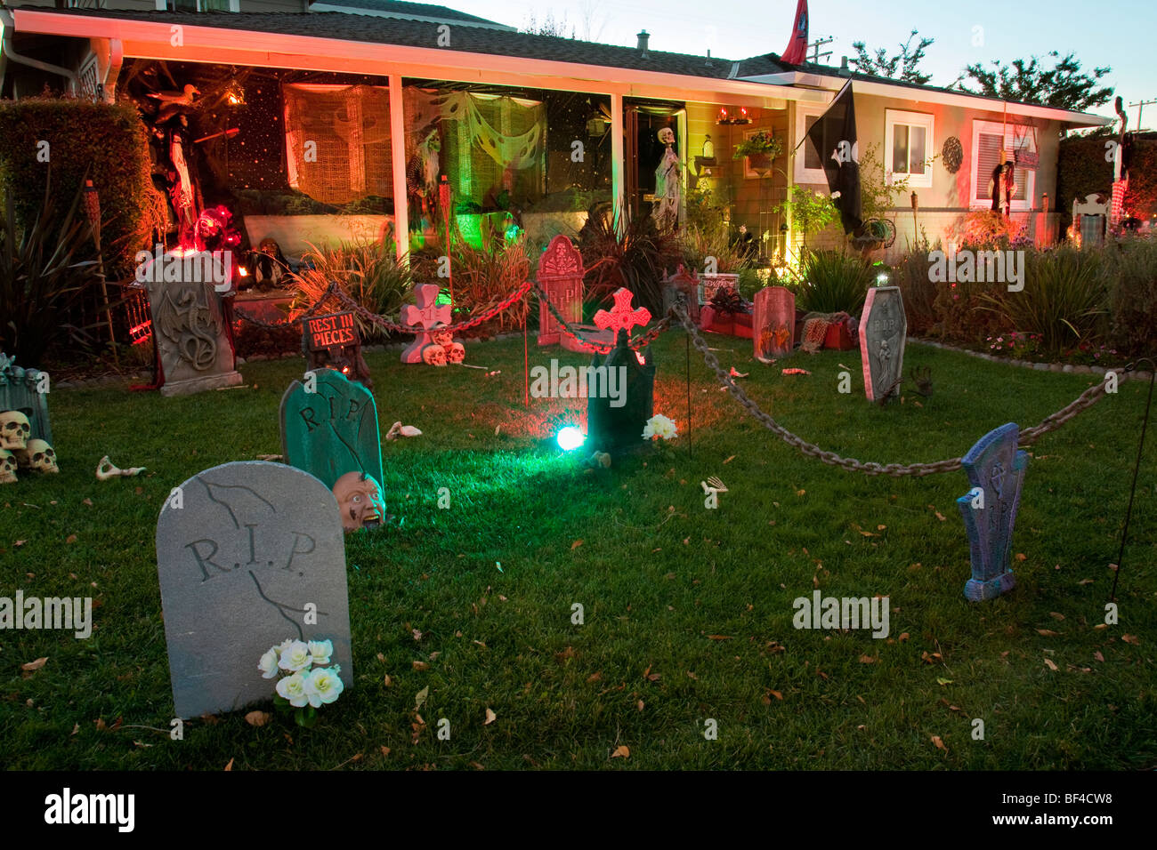 Front lawn decorated as a spooky cemetery for Halloween with tombstones and skeletons - Stock Image