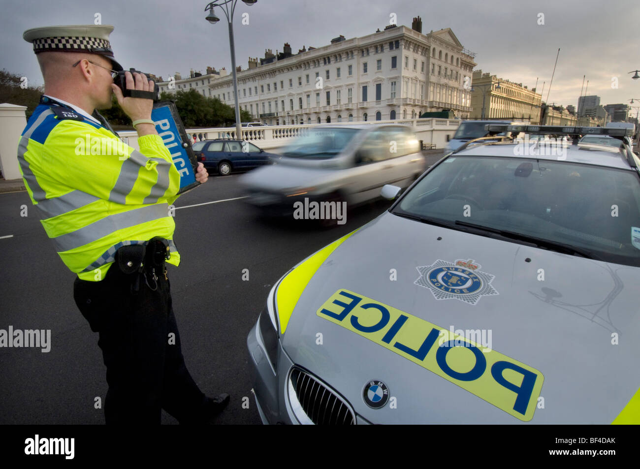 A police officer using a handheld laser camera on a city road to catch speeding motorists - Stock Image