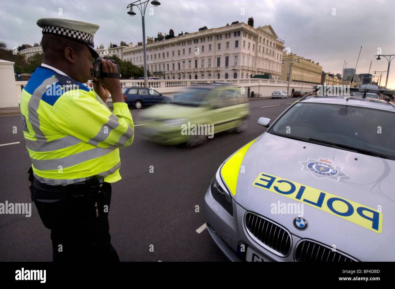 A black police officer using a laser camera to catch speeding motorists - Stock Image