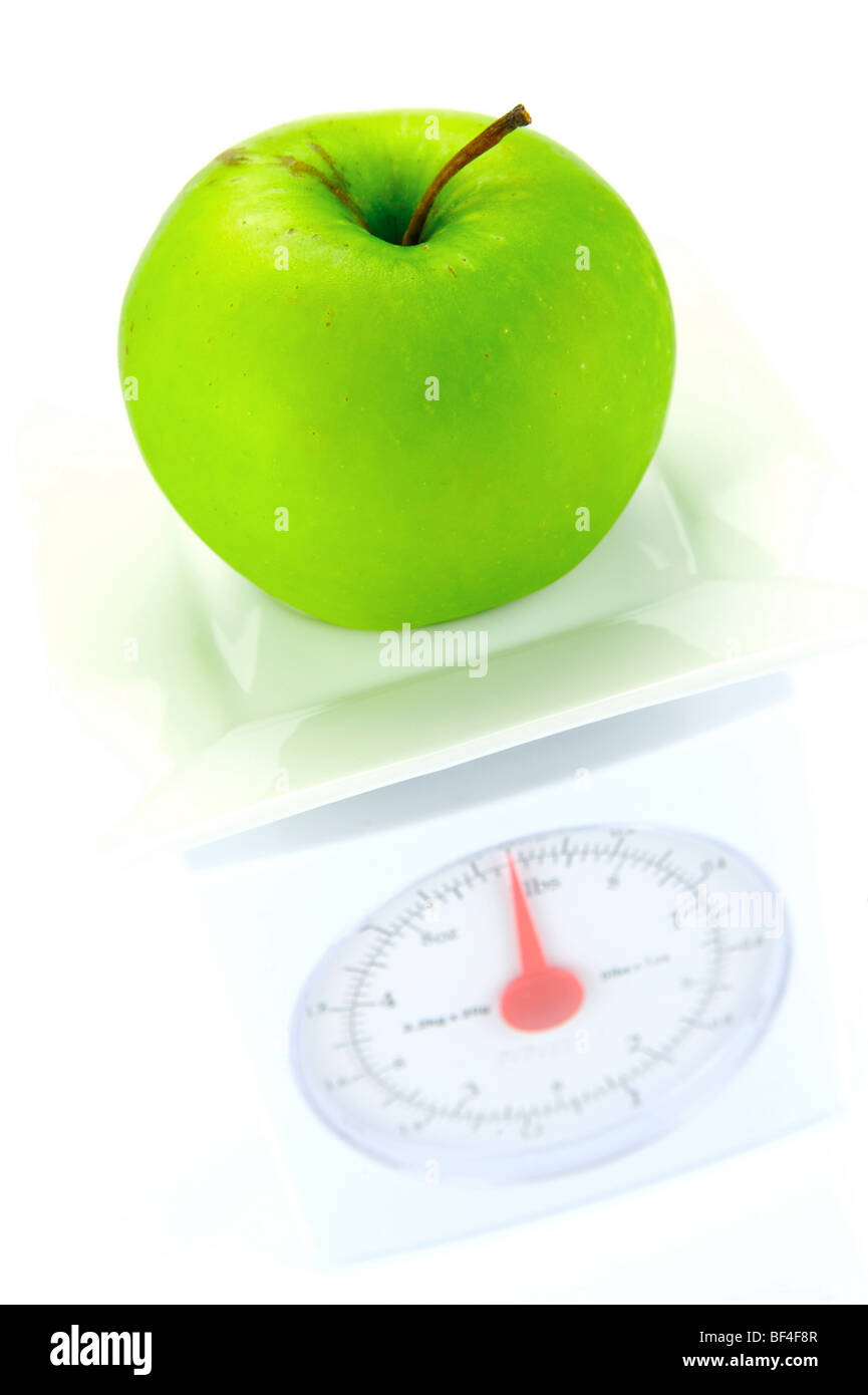 An apple and a set of scales isolated against a white background - Stock Image